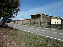 "View from the grass verge of the main N96 road, showing the rear of the Dominicis' farm, ""La Grand' Terre"", abutting the other side of the road."