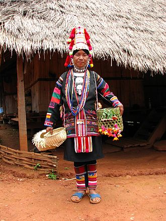 Hill tribe (Thailand) - Akha tribeswoman wearing traditional dress, with baskets and palm-thatched house in northern Thailand
