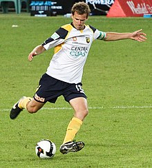 A man wearing a white shirt and navy shorts in the act of kicking a football with his right foot.