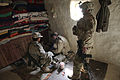 An Afghan Border Police officer searches for contraband in a building as an International Security Assistance Force service member stands by in Bets Kalay village, Kandahar province, Afghanistan, Feb 120227-A-EW551-158.jpg
