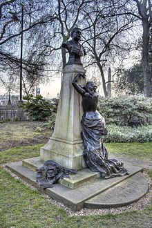 A bronze and stone memorial to Arthur Sullivan. A bronze bust of Sullivan stands on a granite pedestal. A figure of a crying muse leans against the plinth. On the base, bronze sculptures of sheet music, the masks of comedy and tragedy and a mandolin.