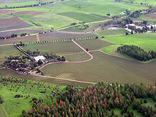 Aerial view of farming fields interspersed with roads, a small forest near the front of the photo