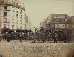 An image of a barricade in the Paris commune. Crowds of people are gathered.