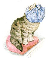 A kitten sitting on a hassock with a dust cloth wrapped over her face and head