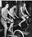 Black & white photograph, portrait orientation, enlarged reproduction, Maurice Bathhouse gymnasium, 2 women on exercise cycles (cb579fdc-09ec-4a64-9574-5eb941f86759).jpg