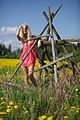 Blond woman in a pink dress on a field with yellow flowers 02.jpg