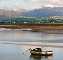 A fishing boat at anchor in the estuary, with mudflats and mountains in the background