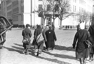 Riga Ghetto - 1942 photo showing Jews in Riga required to wear the yellow star and forbidden to use the sidewalk