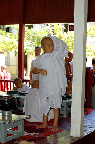 Shinbyu - A boy donning white monastic robes before being ordained as a samanera (shin thamane)