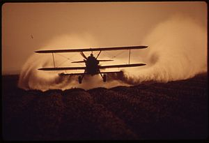 Aerial application - Altitude and wind affect dispersion. Photo by Charles O'Rear, 1972.