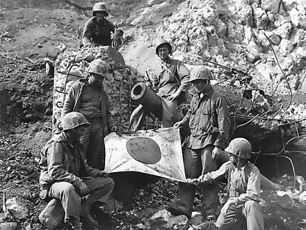 U.S. Marines (Left to Right), PFC. J. L. Hudson Jr. Pvt. K.L. Lofter, PFC. Paul V.Parces, (top of blockhouse), Pvt. Fred Sizemore, PFC. Henrey Noviech and Pvt. Richard N. Pearson pose with a captured Japanese flag on top of enemy pillbox. Captured Japanese flag on Iwo Jima.jpg