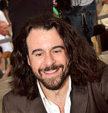 head and shoulders view of a smiling man with a dark beard and long hair, in a dark jacket with open white collar
