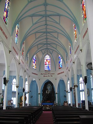 Our Lady of Lourdes Church, Singapore - The Church's interior showing the nave, altar and stained glass windows.