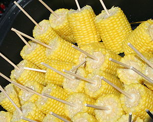 Corn on the cob - Cooked corn on the cob with serving sticks