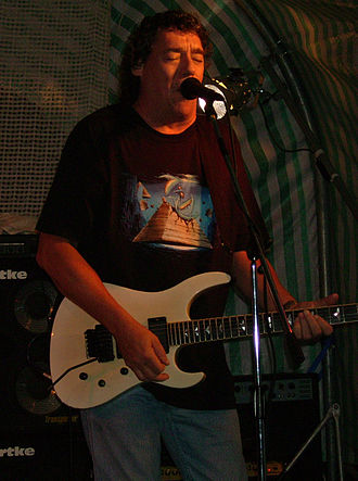 Dennis Stratton - Stratton performing with Praying Mantis, with a T-shirt depicting artwork from Forever in Time