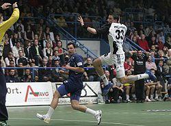 A handball player jumping towards the goal