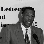 A picture of a darker black man wearing a suit while standing behind a podium. The photograph is in black and white.