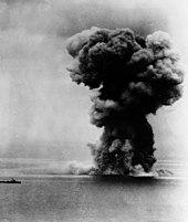 A view of the ocean stretching to the horizon with the silhouette of a distant small warship visible to the left. To the right an enormous mushroom cloud rises high into the sky.