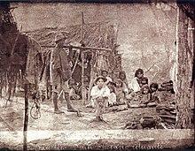 Uma fotografia antiga retratando um grupo de folheados pessoas mal na fronto de uma pequena cabana construída de pequenos galhos de árvores
