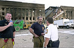 Firefighters discuss rescue operation standing in front of the Western ring of the Pentagon Building hours after American Airlines Fight 77 was piloted by terrorists into the building, during the September 11 010911-N-AV833-014.jpg