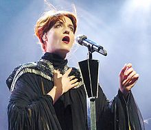 A photograph shot from below Welch as she sings into a microphone