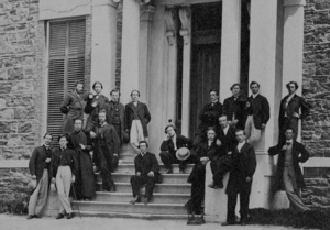 A group of men assembled on the front steps of a building, posed in formal wear.
