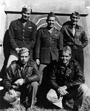 A monochrome photograph of five men wearing military pilot uniforms, three standing, two squatting, in front of a decorative Chinese structure