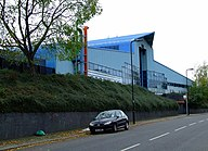 A large, blue, triangular building at the top of a plant covered embankment.