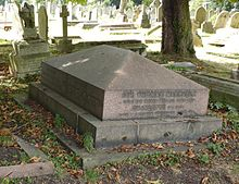 A red granite gravestone geometrically similar to the roof of a house, surrounded by other headstones
