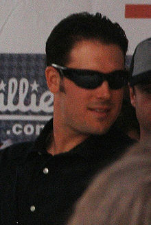 A dark-haired man with sideburns wearing a white shirt and dark sunglasses