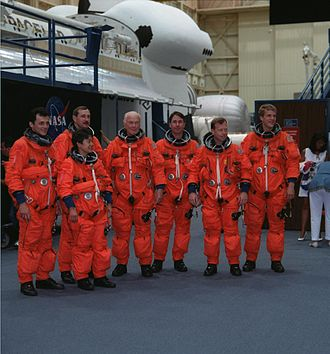 STS-95 - The seven crew members pose for photographers prior to participating in a training session.