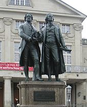 "Photograph of a large bronze statue of two men standing hand-in-hand, side-by-side and facing forward. The statue is on a stone pedestal, which has a plaque that reads ""Dem Dichterpaar/Goethe und Schiller/das Vaterland""."