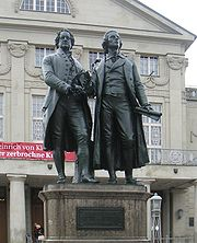 """Photograph of a large bronze statue of two men standing side-by-side and facing forward. The statue is on a stone pedestal, which has a plaque that reads """"Dem Dichterpaar/Goethe und Schiller/das Vaterland""""."""