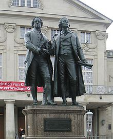"Photograph of a large bronze statue of two men standing side by side and facing forward. The statue is on a stone pedestal, which has a plaque that reads ""Dem Dichterpaar/Goethe und Schiller/das Vaterland""."