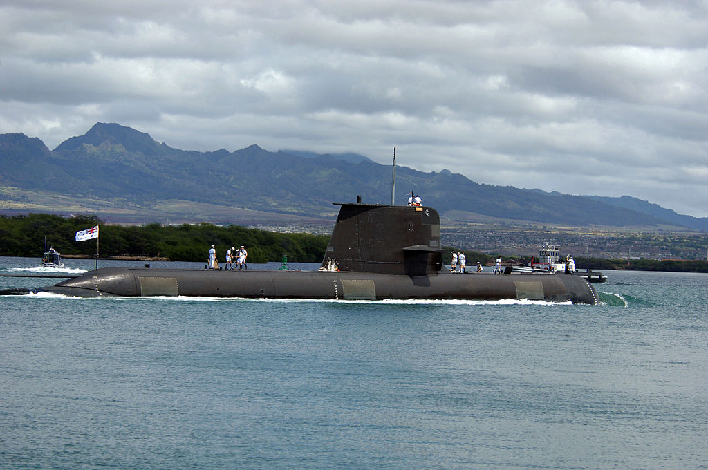 Side view of submarine with sailors on deck, at sea in front of a hilly coast
