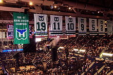 Photo de l'intérieur du Hartford Civic Center avec au premier plan, la bannière de champion de la division Adams 1986-87 des Whalers de Hartford et les 6 maillots retirés de ces mêmes Whalers : de gauche à droite, les numéros 19, 11, 10, 9, 5 et 2.