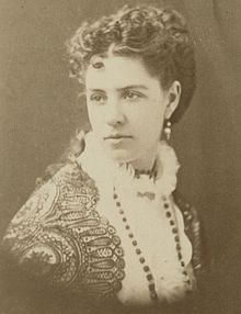A monochrome photograph portrait of a woman 29 or 30 years old, shown from the chest up, wearing a long necklace with dark beads atop a white blouse with an encircling collar made of lace, covered on the shoulders with a dark lace drape, with long, dark hair curled and secured behind the head with tresses down past the shoulder blades, the woman's body turned to the right but her head turned to the left to reveal a dangling earring.