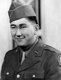 Head and shoulders of a smiling young man with dimples and round wire-framed glasses wearing a garrison cap and a military jacket over a shirt and tie