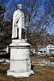A white marble statue of a man wearing 19th century clothing and a long cloak stands atop a tall marble pedestal. The statue stands on a small grassy knoll with bare tree branches and a blue sky in the background.