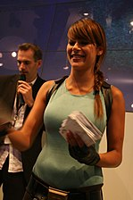 A half body picture of a brunette woman dressed in a light blue, sleeveless shirt holding a stack of papers.