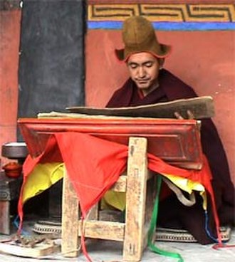 Traditional knowledge - Buddhist monk Geshe Konchog Wangdu reads Mahayana sutras from an old woodblock copy of the Tibetan Kanjur.