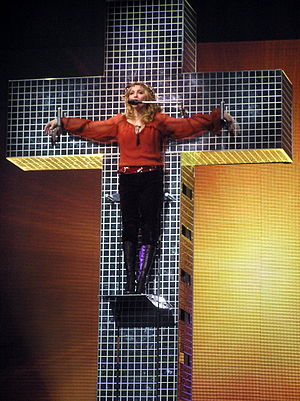 "Confessions Tour - Madonna hanging from a cross while performing ""Live to Tell"". The performance faced strong reactions from religious leaders who condemned it as anti-Christ."