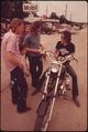 MOTORCYCLIST FROM LEAKEY, TEXAS, STOPS TO TALK WITH FRIENDS NEAR SAN ANTONIO - NARA - 554875.tif