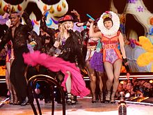 Madonna and her dancers in colorful cloths dancing onstage.