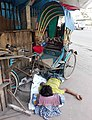 Man.taking rest under a rickshaw at dhaka .jpg