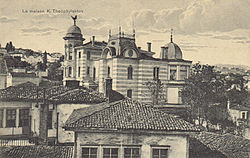 Sepia photograph of a mansion among smaller houses in a city.