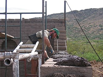 Masonry - A mason laying mortar on top of a finished course of blocks, prior to placing the next course.