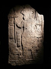 An upright stone slab with the front face flat and inscribed with two elaborately dressed figures facing each other, with a double column of hieroglyphs between them.