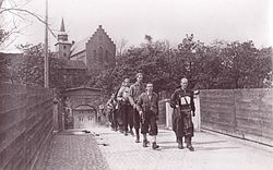 Ragtag group of men with guns marching away from a walled fortress