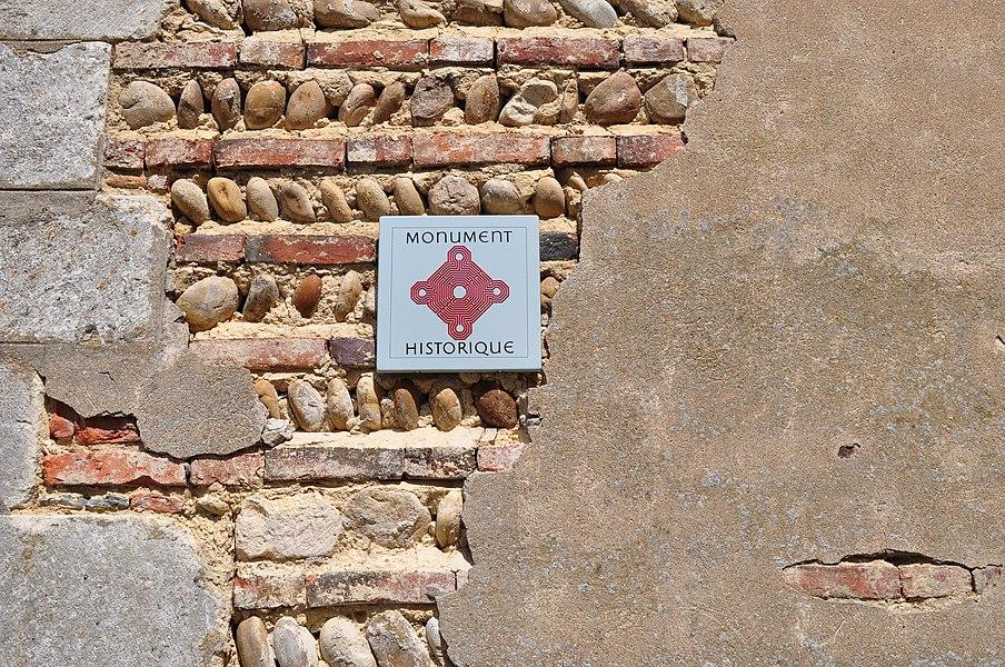 Le mur de l'église de Bouligneux, où on voit la construction en briques / galets / pisé recouverts.